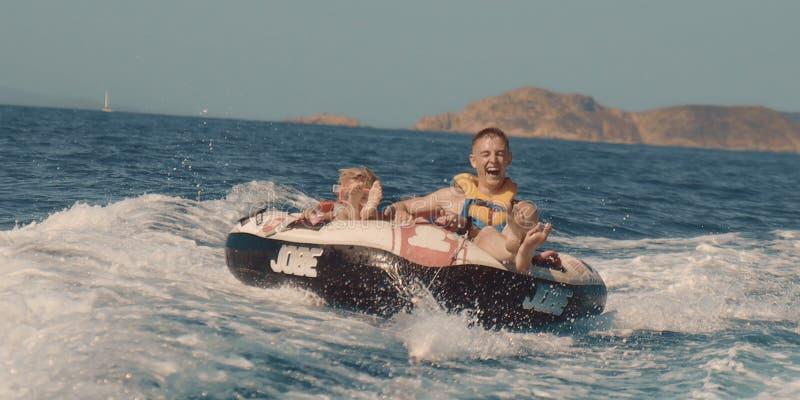Adolescente y niño pequeño que ríen mientras que siendo tirado por un barco en un buñuelo inflable en el océano en St Tropez Fran fotos de archivo libres de regalías