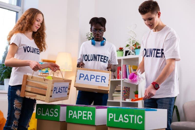 Adolescentes activos que separan el papel del plástico mientras que clasifica la basura foto de archivo