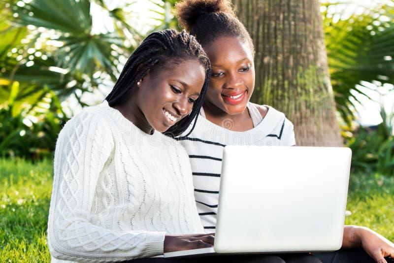 Adolescentes africanos que jogam no portátil no parque imagens de stock