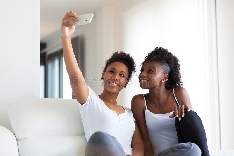 Adolescentes afro-americanos que tomam uma imagem do selfie com uma manutenção programada imagem de stock