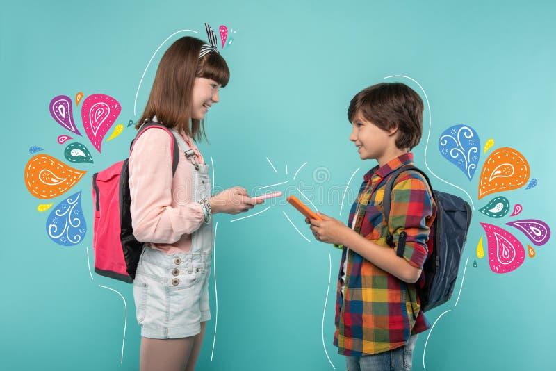 Adolescentes alegres que sorriem e que trocam seus números de telefone imagens de stock