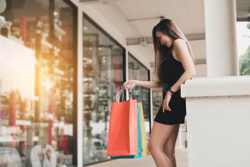 Adolescentes asiatiques tenant et tenant des sacs à provisions au centre commercial photo stock
