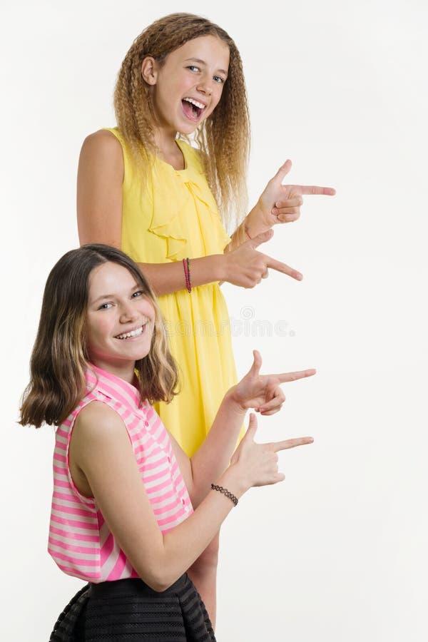 Adolescentes atrativos do positivo dois que apontam seu indicador afastado imagem de stock royalty free
