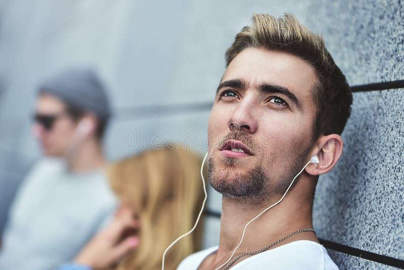 Adolescentes atrativos novos que escutam a música nos mesmos pares de fones de ouvido, vestidos na roupa à moda contra um fundo d imagens de stock