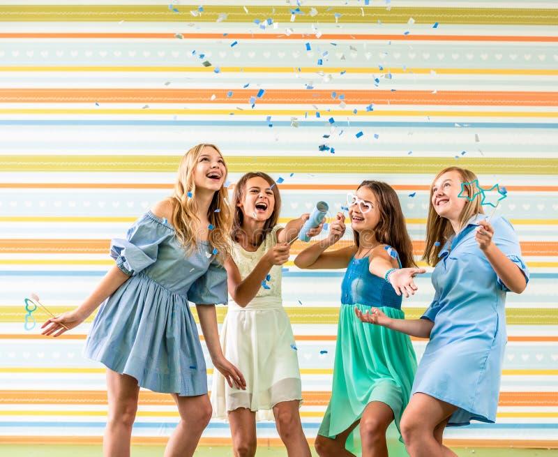 Adolescentes bastante sonrientes en los vestidos alegre que funcionan con las chapaletas en fiesta de cumpleaños fotografía de archivo
