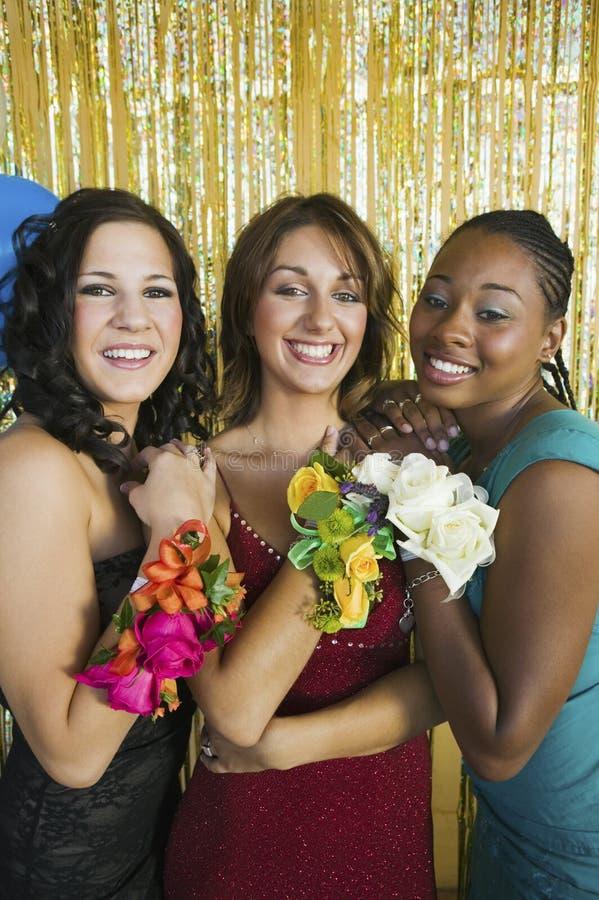 Adolescentes bien vestidos que muestran los ramilletes en el retrato de la danza de la escuela fotografía de archivo libre de regalías