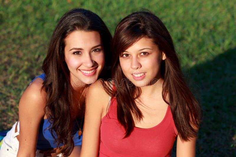 Adolescentes bonitos de la universidad que disfrutan de vida del campus imagenes de archivo
