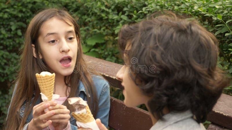 Adolescentes bonitos, menino e menina comendo o gelado no parque e na fala imagem de stock