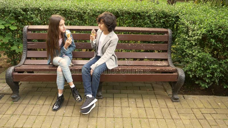 Adolescentes bonitos, menino e menina comendo o gelado no parque e na fala fotos de stock royalty free