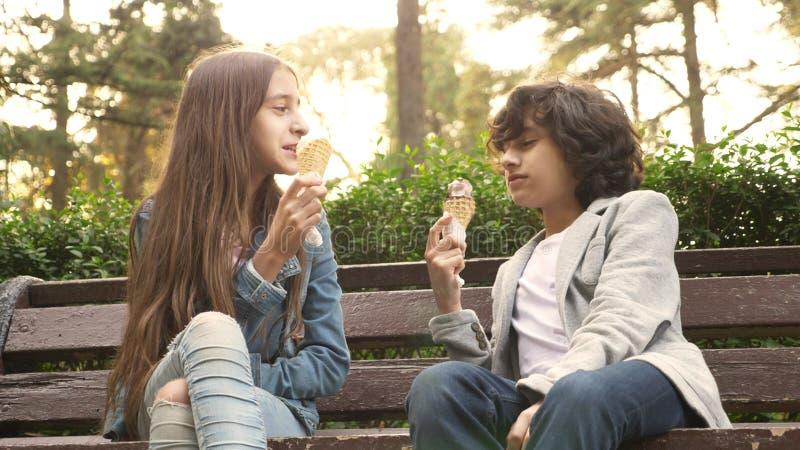 Adolescentes bonitos, menino e menina comendo o gelado no parque e na fala fotografia de stock