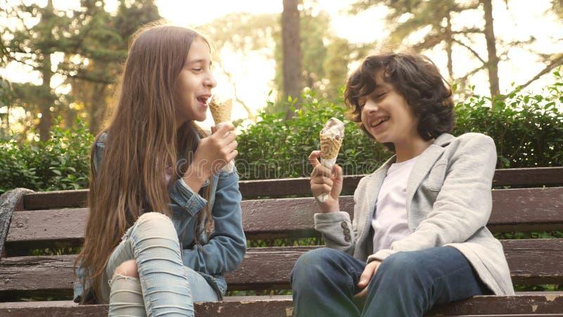 Adolescentes bonitos, menino e menina comendo o gelado no parque e na fala foto de stock royalty free