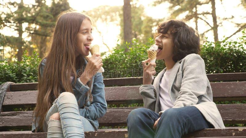 Adolescentes bonitos, menino e menina comendo o gelado no parque e na fala imagens de stock royalty free