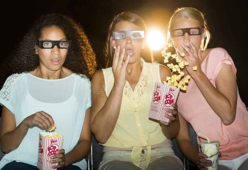 Adolescentes chocados que miran la película 3D en teatro imagenes de archivo