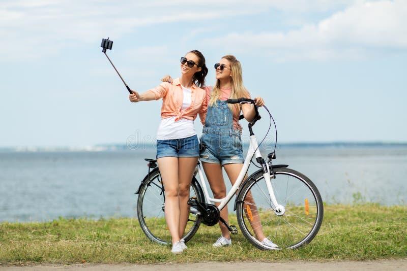 Adolescentes com a bicicleta que toma o selfie no verão imagens de stock