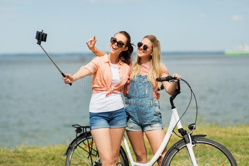 Adolescentes com a bicicleta que toma o selfie no verão imagem de stock