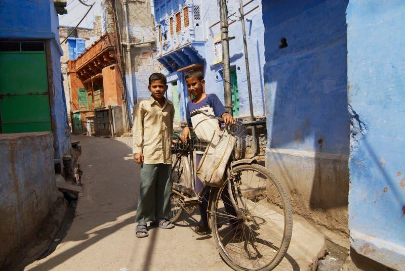 Adolescentes com um suporte velho da bicicleta na rua estreita com as casas pintadas azuis em Jodhpur, Índia fotografia de stock royalty free