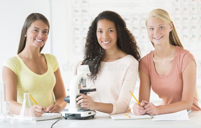 Adolescentes con el microscopio en el escritorio en clase de química foto de archivo