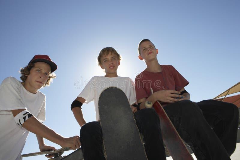 Adolescentes con los monopatines contra el cielo azul imagen de archivo