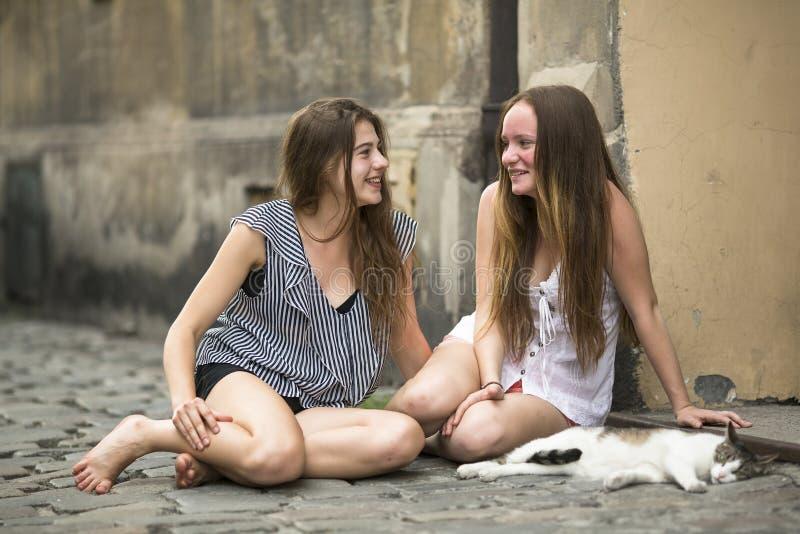 Adolescentes d'amies s'asseyant sur le trottoir avec un chat image stock