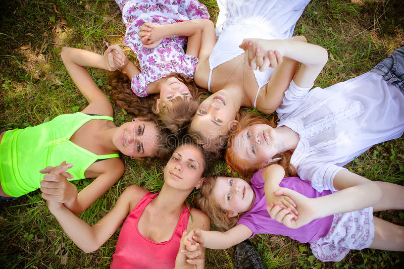 Adolescentes das meninas no parque na grama fotos de stock