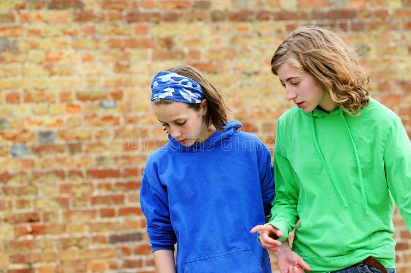 Adolescentes de encontro à parede de tijolo fotos de stock