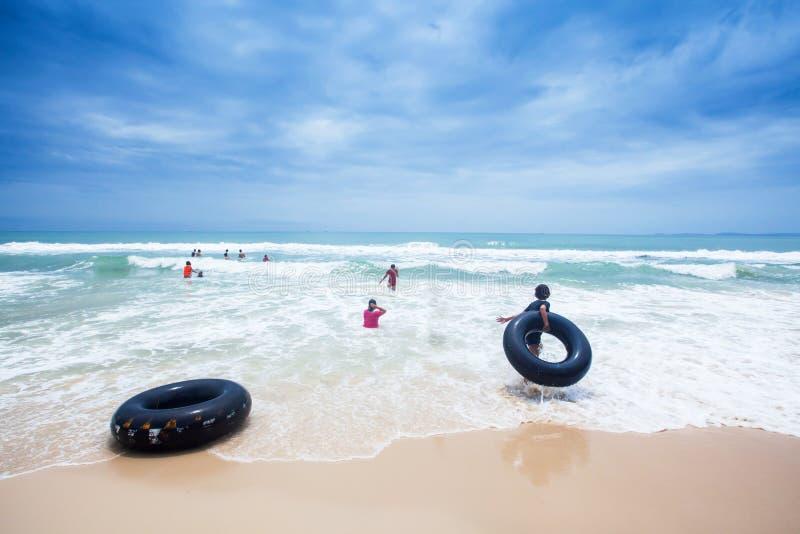 Adolescentes de Khmer jouant dans les vagues sur la plage d'Ochheuteal dans un jour pluvieux images libres de droits