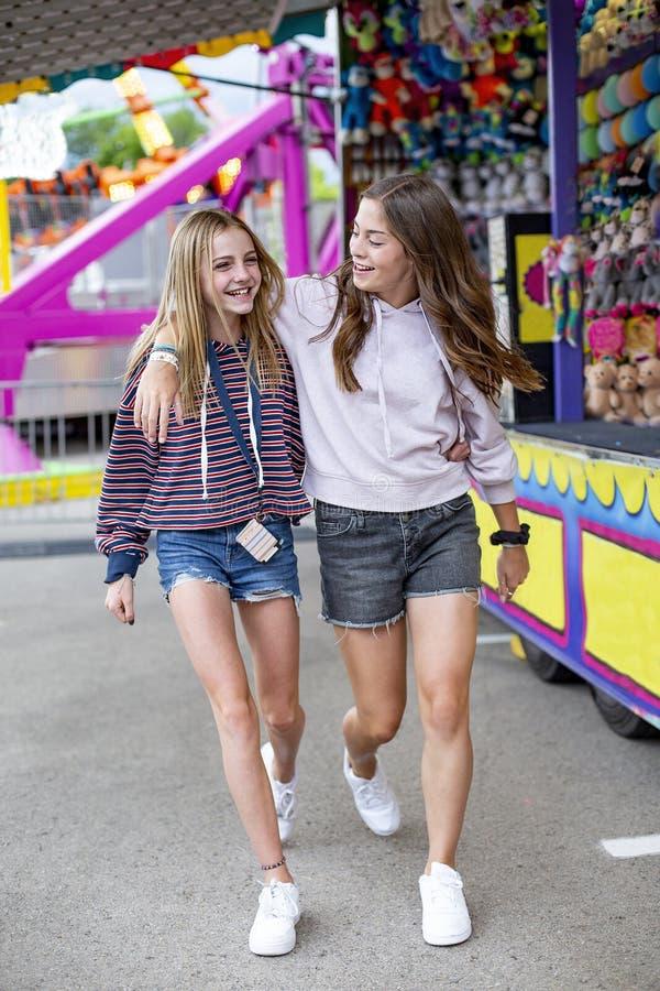 Adolescentes de sorriso que têm o divertimento em um carnaval exterior do verão fotos de stock