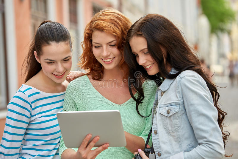 Adolescentes de sourire avec le PC et l'appareil-photo de comprimé photographie stock libre de droits