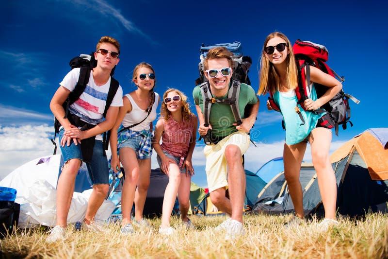 Adolescentes delante de las tiendas con las mochilas, festival del verano fotos de archivo libres de regalías