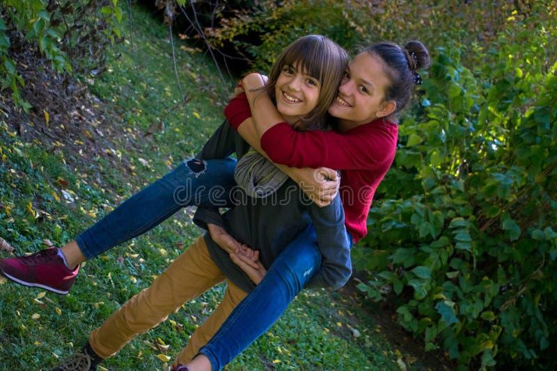 Adolescentes despreocupados que rebocam durante o dia no parque imagem de stock