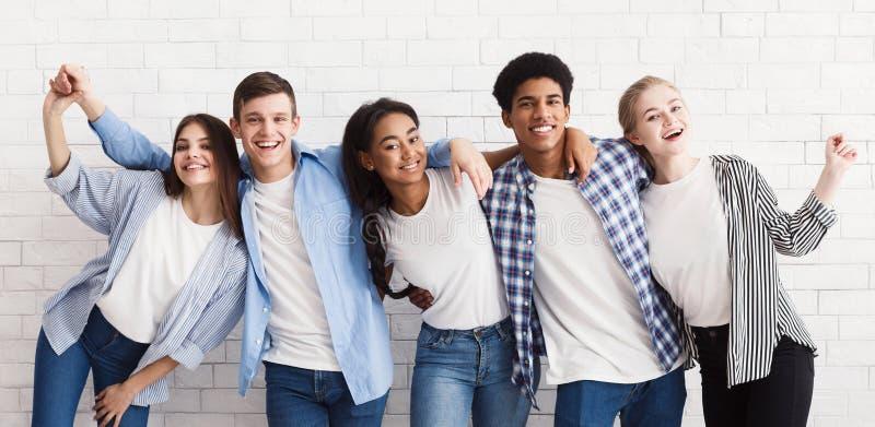 Adolescentes diversos que abrazan y que se divierten sobre la pared blanca foto de archivo