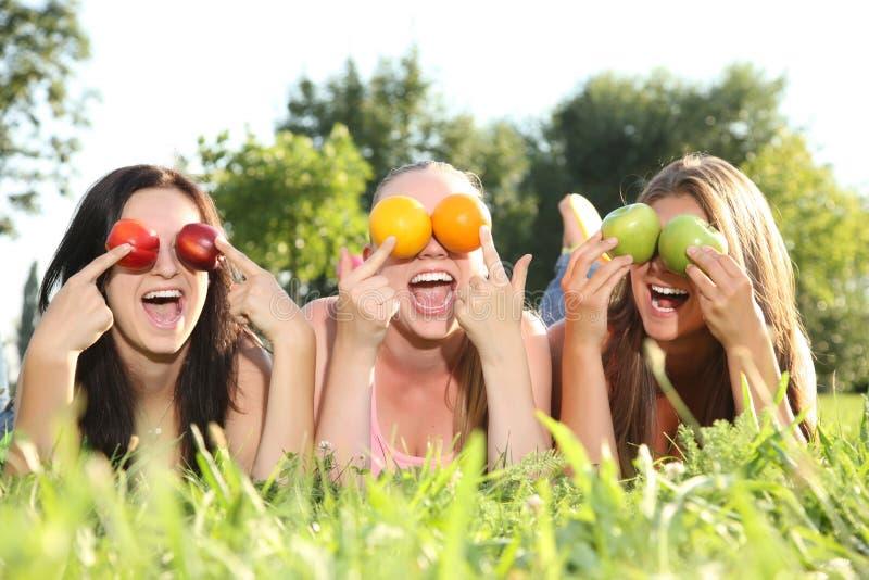 Adolescentes divertidos que presentan en la hierba imagenes de archivo