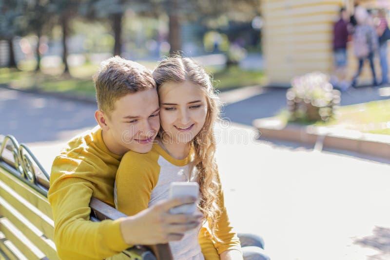 Adolescentes dos pares em um banco foto de stock