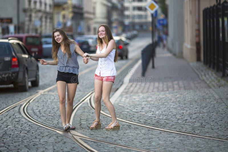Adolescentes drôles marchant ensemble sur le trottoir sur la rue images stock
