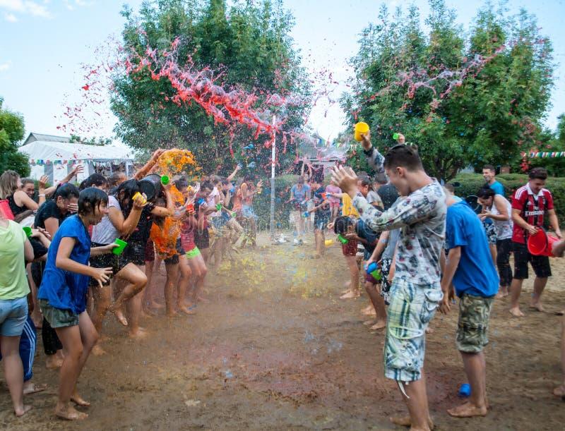 Adolescentes e crianças que espirram na água colorida no acampamento de verão imagens de stock