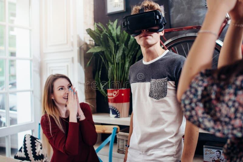 Adolescentes emocionais que usam auriculares de VR para olhar os filmes 3D ou os jogos do jogo que penduram para fora em casa foto de stock