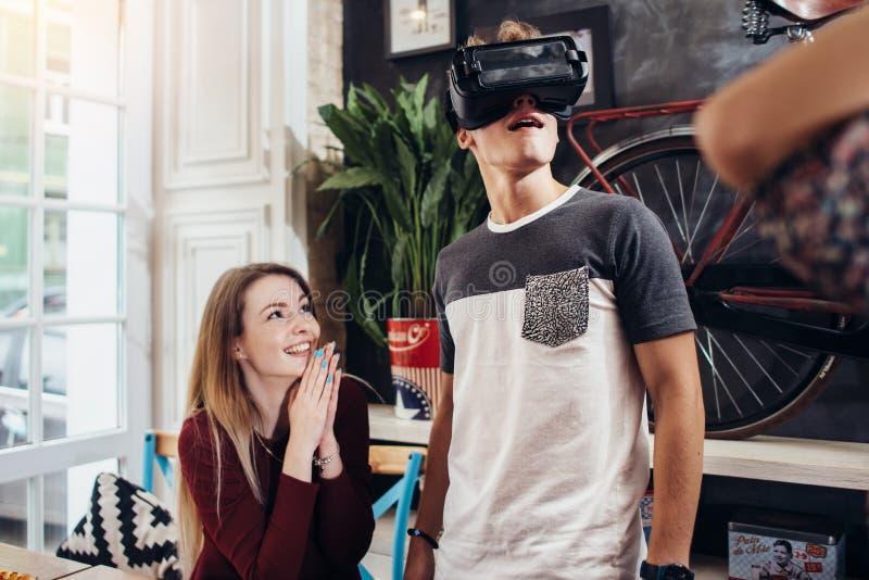 Adolescentes emocionales que usan las auriculares de VR para mirar las películas 3D o los juegos del juego que cuelgan hacia fuer imagen de archivo