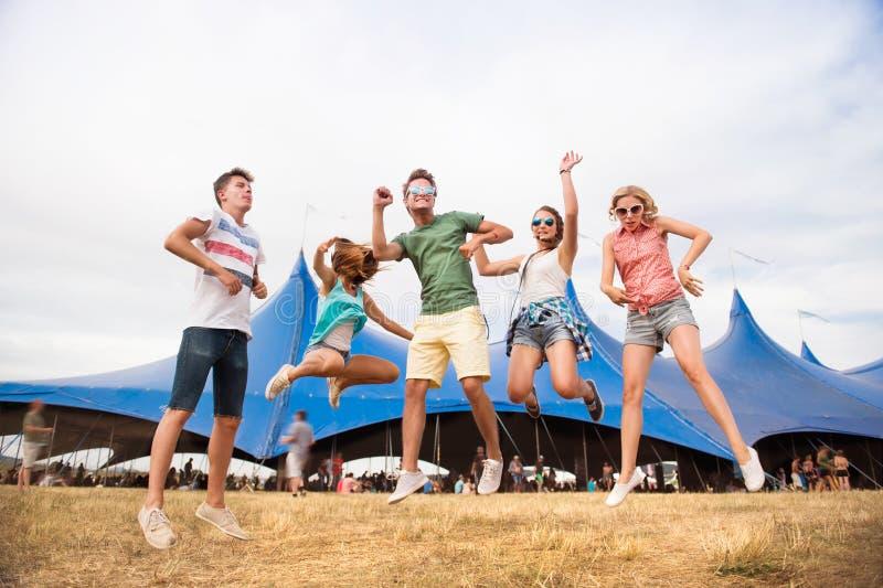 Adolescentes en el baile y el salto del festival de música del verano fotografía de archivo