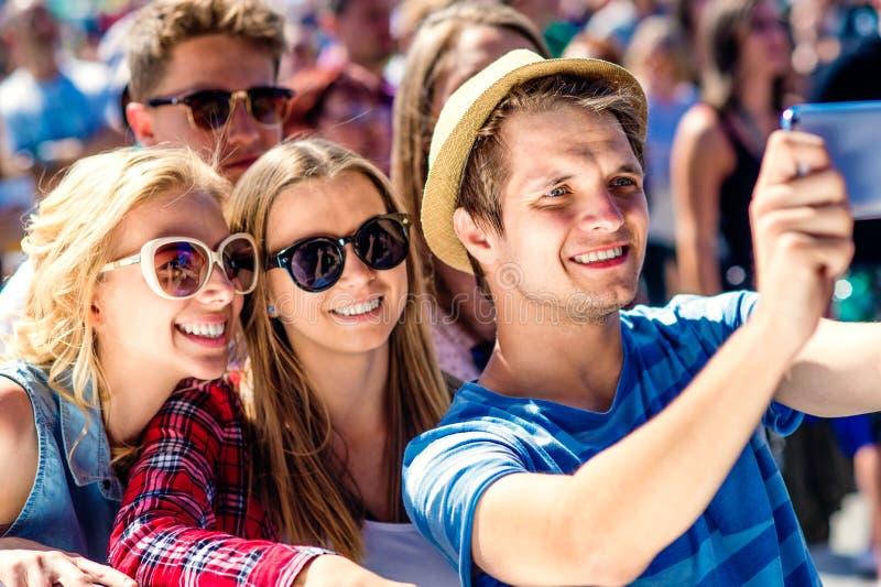 Adolescentes en el festival de música del verano en la muchedumbre que toma el selfie fotografía de archivo libre de regalías