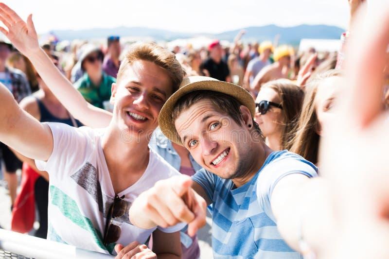 Adolescentes en el festival de música del verano en la muchedumbre que toma el selfie imagenes de archivo