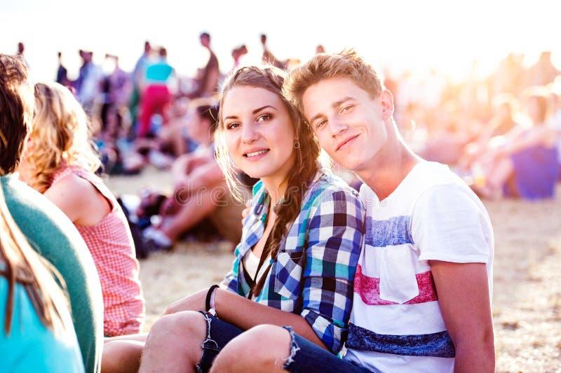 Adolescentes en el festival de música del verano, sentándose en la tierra fotografía de archivo