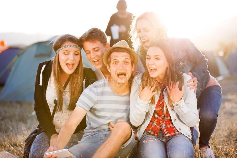 Adolescentes en el festival de música del verano, tomando el selfie con el smartphon fotografía de archivo libre de regalías