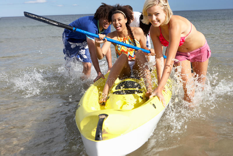 Adolescentes en el mar con la canoa imagenes de archivo