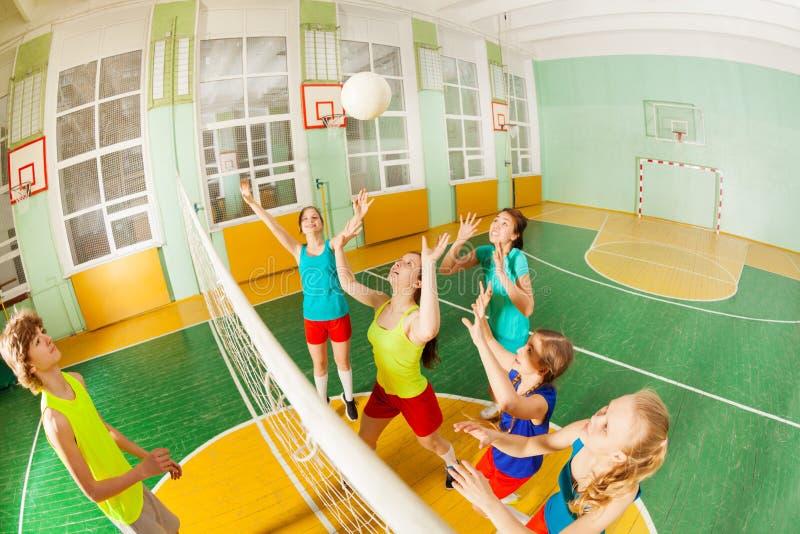 Adolescentes en la acción durante partido del voleibol foto de archivo