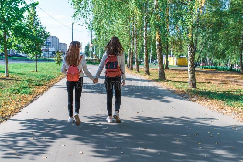 Adolescentes en pull, vue arrière, marche avec sac à dos derrière, été en automne et printemps en ville, week-end après photographie stock