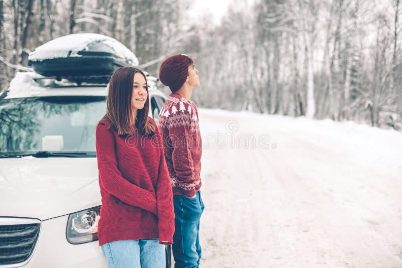 Adolescentes en suéteres de la Navidad que caminan en nieve en invierno foto de archivo