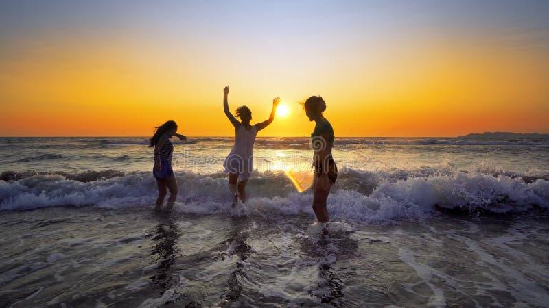 adolescentes fêmeas que têm o divertimento que salta e que espirra abaixo da praia no por do sol imagens de stock royalty free