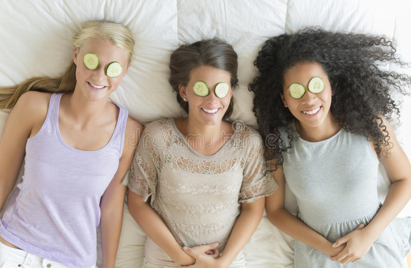 Adolescentes felices con las rebanadas del pepino en sus ojos foto de archivo libre de regalías