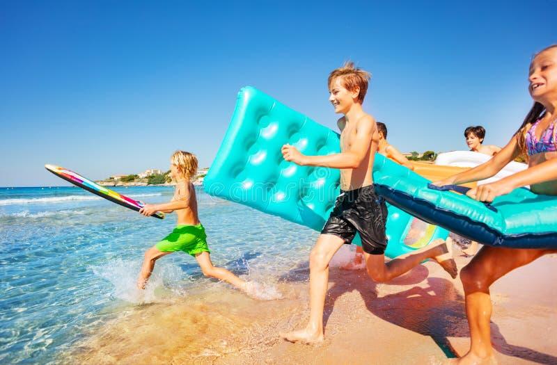Adolescentes felices que corren en el mar en verano fotos de archivo