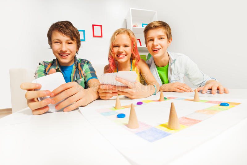 Adolescentes felices que juegan al juego de tabla que sostiene tarjetas imágenes de archivo libres de regalías